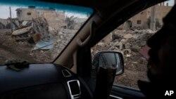 ນັກລົບ ຂອງກຳລັງເພື່ອປະຊາທິປະໄຕ ໃນຊີເຣຍ Syrian Democratic Forces (SDF) ທີ່ໄດ້ຮັບການໜຸນຫຼັງໂດຍ ສະຫະລັດ ຂີ່ລົດຜ່ານເຮືອນຊານ ແລະລົດຫຼາຍໆຄັນ ທີ່ໄດ້ຖືກທຳລາວ ແລະ ຢູ່ໃນຄຸ້ມບ້ານແຫ່ງນຶ່ງ ໃນເມືອງ ຊູຊາ ຈາກການເຂົ້າຍຶດເອົາຄືນ ຈາກກຸ່ມຫົວຮຸນແຮງ ລັດອິສລາມ ໃນຊີເຣຍ, ວັນທີ 16 ກຸມພາ 2019.