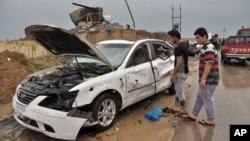 2014年4月13日伊拉克巴格達: 伊拉克平民查看自殺式汽車炸彈爆炸場地。