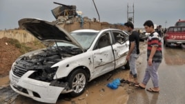 Iraq civilians inspect the site of a suicide car bombing in the northern town of Dibis, near Kirkuk, 290 kilometers north of Baghdad, Iraq, April 13, 2014.