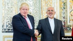 Iran's Foreign Minister Mohammad Javad Zarif shakes hands with Britain's Foreign Secretary Boris Johnson during their meeting in Tehran, Dec. 9, 2017.