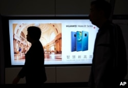 People walk past an advertisement for Huawei at a subway station in Hong Kong, Dec. 5, 2018. Canadian authorities said they have arrested Huawei's chief financial officer Meng Wanzhou.