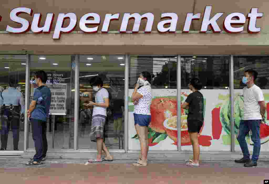 مشتریان در صف سوپرمارکت در مانیل فیلیپن بین هم فاصلهای گذاشته اند تا گرفتار کرونا نشوند!