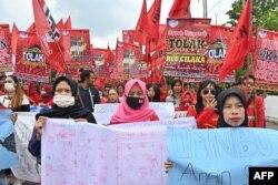 Para pekerja berpawai menuju gedung DPR/MPR untuk memprotes rancangan undang-undang omnibus penciptaan lapangan kerja, di Jakarta, 13 Januari 2020. (Foto: AFP)
