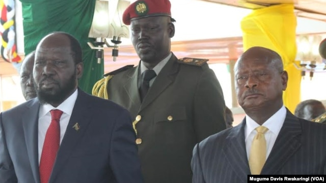 South Sudanese President Salva Kiir (left) watches an Independence Day parade in Juba on July 9, 2014 with Ugandan President Yoweri Museveni (right).