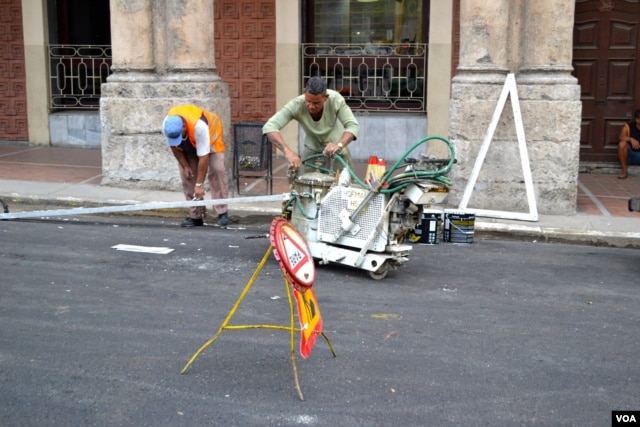 Workers make repairs on a road in Havana.