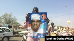 Un homme tient une affiche de campagne de Hama Amadou, candidat à la présidentielle nigérienne.