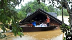 A girl stands on a boat in front of her flooded home in central Ha Tinh province, 05 Oct. 2010