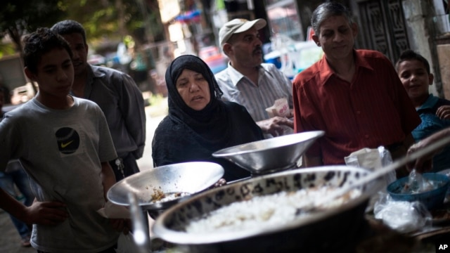 FILE - An Egyptian woman waits for her breakfast on a street fast food restaurant in Suleiman Gohar market in Dokki district in Cairo, Egypt.