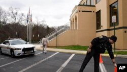 A Loudoun County (Va.) sheriff's deputy moves a traffic cone at the All Dulles Area Muslim Society Center in Sterling, Va., where security guards resigned because they felt they could no longer protect the mosque amid anti-Muslim sentiment, Dec. 18, 2015.