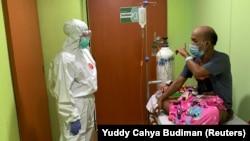 Dokter Cheras Sjarfi berbincang dengan seorang pasien di ruang isolasi di tengah lonjakan kasus baru COVID-19, di sebuah rumah sakit di Jakarta, 1 Juli 2021. (Foto: Yuddy Cahya/Reuters)