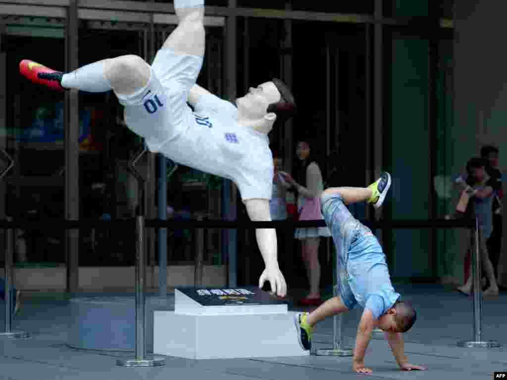 Seorang anak laki-laki berpose untuk difoto di depan patung pemain sepak bola Inggris Wayne Rooney di pintu masuk sebuah mal di Beijing, China.