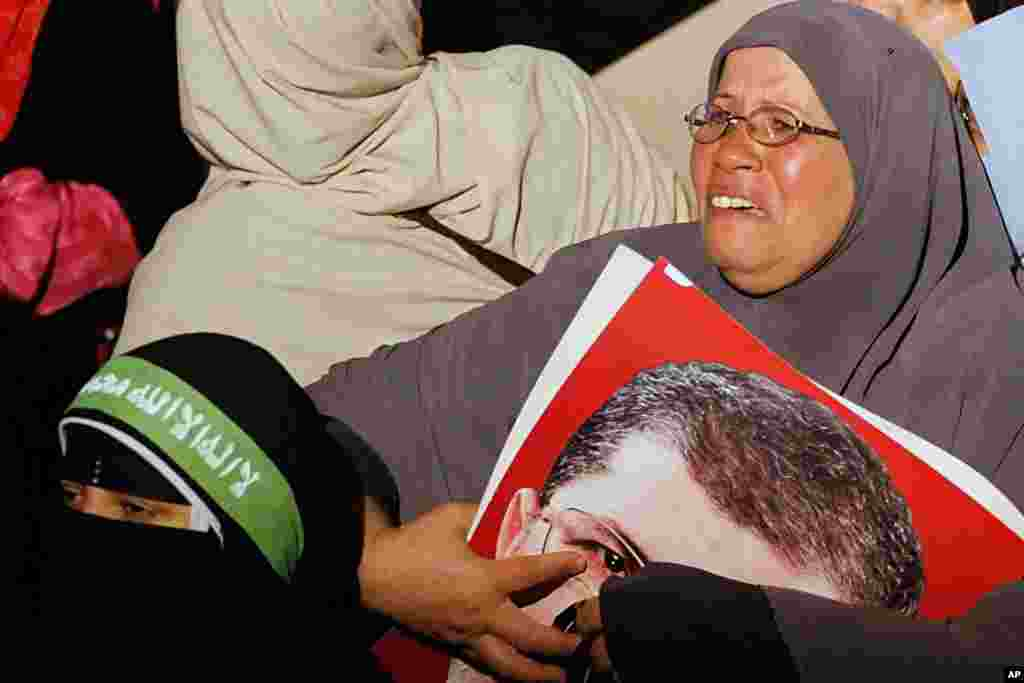 A supporter of Egypt's ousted president Mohamed Morsi weeps as she clutches his picture after the Minister of Defense's announcement on state television, in Cairo, July 3, 2013.