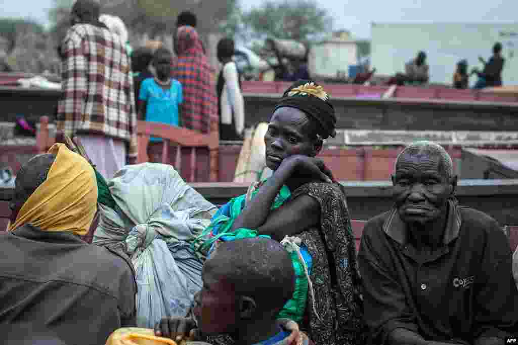 People unload the few belongings on Jan. 9, 2014 at Minkammen, South Sudan, that they were able to bring with them to camps for the displaced.