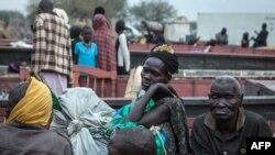 Warga di Minkammen, Sudan Selatan, mengangkut sedikit harta bendanya untuk mengungsi (9/1). (AFP/Nichole Sobecki)