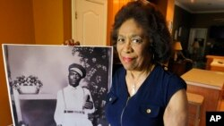 Josephine Bolling McCall poses with a photo of her father, lynching victim Elmore Bolling, at her home in Montgomery, Alabama, April 18, 2018. Bolling is among thousands of lynching victims remembered at the new National Memorial for Peace and Justice, erected with donations by the Alabama-based Equal Justice Initiative. The memorial and an accompanying museum, which aim to tell the story of racial oppression in the United States, open April 26.