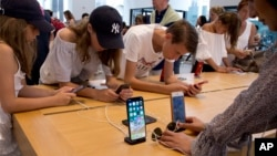 FILE- Customers browse in an Apple store in New York, Aug. 2, 2018. On Thursday, the Commerce Department issued its July report on consumer spending, which accounts for roughly 70 percent of U.S. economic activity.