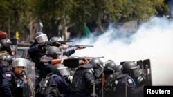 在曼谷政府大厦附近发生的冲突中,泰国防暴警察把武器对准反政府示威者。(2014年2月18日)