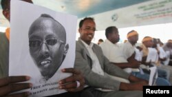 A Somali journalist holds a poster bearing the image of Abdiaziz Abdinur in Mogadishu in this January 27, 2013, file photo..