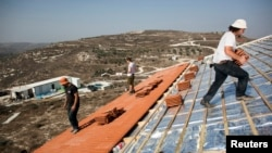 FILE - Men work on the roof of a house under construction in the unauthorized Jewish settler outpost of Havat Gilad, south of the West Bank city of Nablus, Nov. 5, 2013.