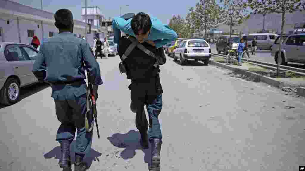 An Afghan policeman carries a wounded man at the site of a suicide attack in Kabul, Afghanistan, Aug. 10, 2014.