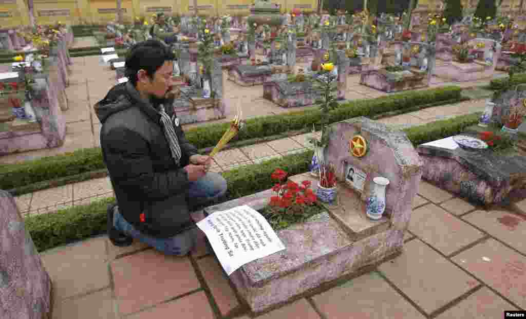 Anti-China protester Anh Chi prays at the grave of Nguyen Xuan Chinh who died during the border war of China and Vietnam, at a military cemetery outside Hanoi February 16, 2014.