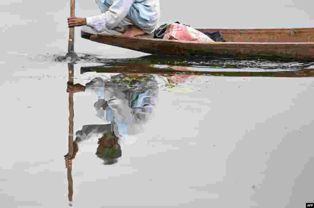 A Kashmiri fisherman rows a boat after a rainfall in Srinagar.