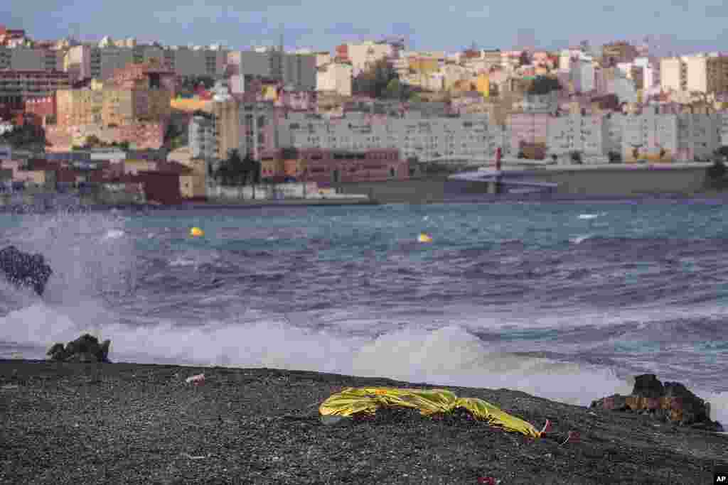 The body of a young man is seen covered with an emergency blanket after being recovered by Spanish police from waters near the border between Morocco and Spain's north African enclave of Ceuta.