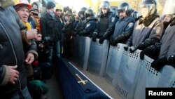 Interior Ministry officers stand guard as European integration supporters hold a rally, with a symbolic coffin seen in the middle, near the residence of Ukraine's President Viktor Yanukovych, outside Kyiv, Dec. 29, 2013.