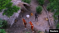 FILE - Members of an uncontacted Amazon Basin tribe and their dwellings are seen during a flight over the Brazilian state of Acre along the border with Peru in this May 2008 photo distributed by Funai, the government agency for the protection of indigenous people.