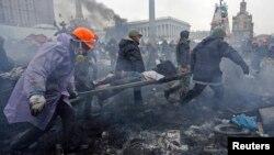 Manifestantes antigubernamentales cargan a un herido luego de enfrentamientos con policías antimotines en la Plaza de la Independencia, en Kiev.