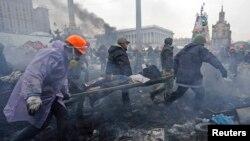 Người biểu tình chống chính phủ khiêng người bị thương trên cáng sau cuộc đụng độ với cảnh sát chống bạo động ở Quảng trường Ðộc lập tại Kyiv, ngày 20/2/2014.