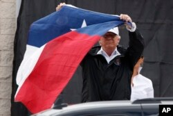 FILE - President Donald Trump holds up a Texas flag after speaking with supporters outside Firehouse 5 in Corpus Christi, Texas, Aug. 29, 2017, where he received a briefing on Harvey relief efforts.