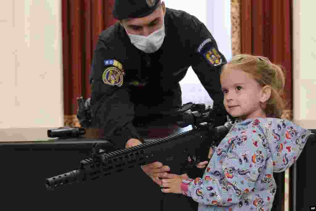 Devojčica pozira sa oružjem na izložbi organizovane od strane rumunske žandarmerije na Međunarodni dan dece u Bukureštu. Više od deset hiljada dece i odraslih posetilo je izložbu. 1. juni, 2021. ( Foto: Vadim Đirda / AP )