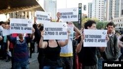 6月9日,在巴西圣保罗的一个地铁站外,当地居民举着支持地铁罢工工人的标语