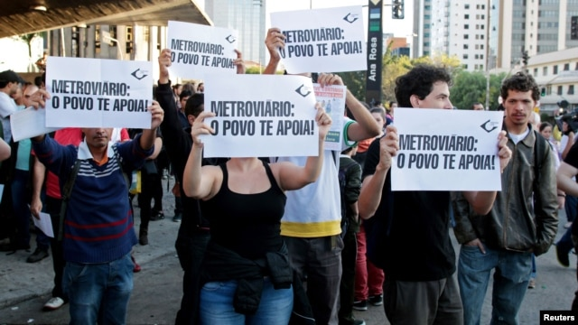 "Residents hold up signs that read, ""Metro workers: The people support you,"" outside Ana Rosa subway station during the fifth day of metro worker's strike in Sao Paulo, Brazil, June 9, 2014."