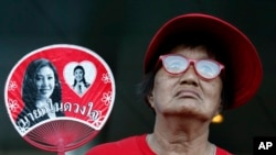 A supporter of Thai former Prime Minister Yingluck Shinawatra holds a fan outside the Supreme Court in Bangkok, Thailand, Wednesday, Sept. 27, 2017. (AP Photo/Sakchai Lalit)
