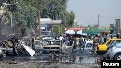 Petugas keamanan Irak memeriksa kendaraan yang hancur akibat serangan bom di Khazimiyah, Baghdad (15/8).
