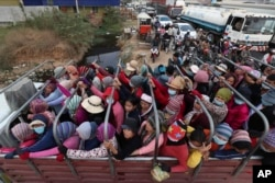 Cambodian garment factory workers ride on the back of a truck as they head to their homes at the evening traffic jump of Sre Cheah village outside Phnom Penh, Cambodia, Saturday, Jan. 11, 2020. (AP Photo/Heng Sinith)