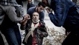 Čovek pomaže ranjenom civilu u napadu na Alepo u Siriji