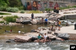 People cool off in the water at the confluence of the South Platte River and Cherry Creek in Denver, Wednesday June 16, 2021. A heat wave continues to hover over the western U.S., pushing the temperature to 99 degrees in Denver. (AP Photo/Brittany Peterso