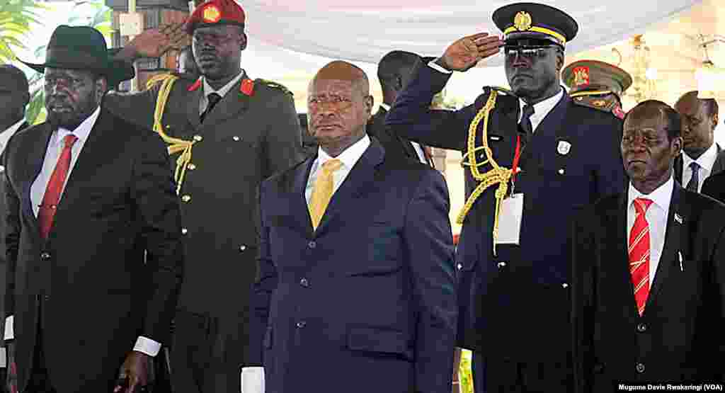 South Sudanese President Salva Kiir (left), Ugandan President Yoweri Museveni (C.) and South Sudan Vice President James Wani Igga (right) stand to attention as South Sudan marks its 4th anniversary of independence on Thursday, July 9, 2015.