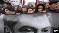 FILE - Russia's opposition supporters carrying a banner bearing a portrait of slain Kremlin critic Boris Nemtsov during a march in central Moscow, March 1, 2015.