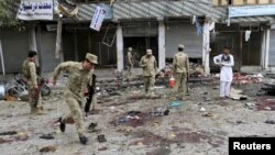 Afghan security force members inspect the site of a suicide attack in Jalalabad, April 18, 2015.