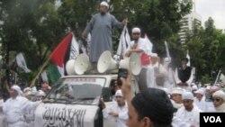 Juru bicara FPI Munarman (berkaca mata hitam, di atas mobil) dalam sebuah aksi demonstrasi. Perlakuannya menyiram lawan debatnya dalam sebuah program TV banyak mengundang kecaman.
