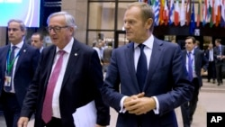 European Commission President Jean-Claude Juncker, left, and European Council President Donald Tusk, right, walk through the atrium during an EU summit in Brussels, Oct. 19, 2017.