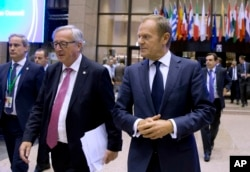 FILE - European Commission President Jean-Claude Juncker, center left, and European Council President Donald Tusk, center right, walk through the atrium during an EU summit in Brussels Oct. 19, 2017.