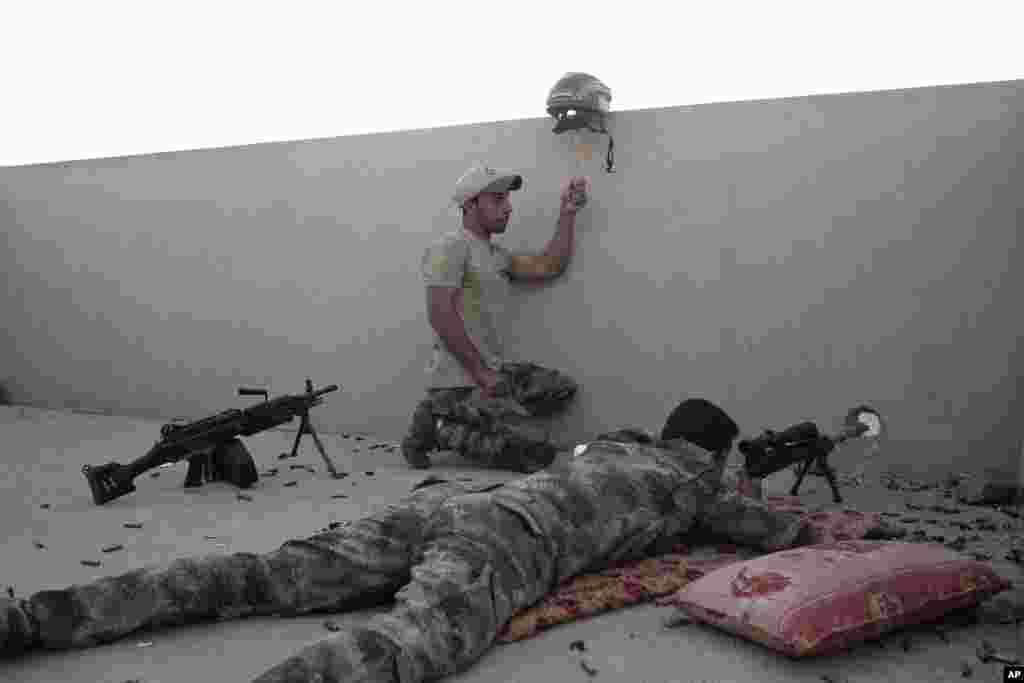 Tentara Irak memegang helm sebagai jebakan (tipuan) sementara rekannya siap menembak ke arah posisi militan ISIS di Gogjali, kota Mosul bagian timur.
