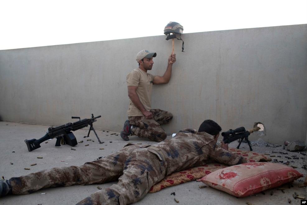 İraq xüsusi qüvvələrinin əsgəri snayperin diqqətini cəlb etmək üçün helmeti qaldırır. Mosul, İraq.