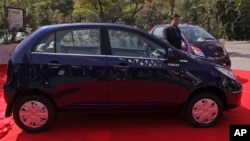 India's Tata Motors National Sales head, Ashesh Dhar poses with the new Tata Vista VX Tech, front, and Nano Twist during their launch in Hyderabad, India, Jan. 21, 2014.