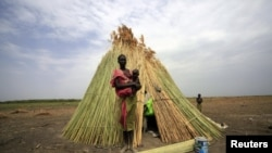 A woman from the Dinka tribe stands in front of her shelter near Bor, Jonglei state, in South Sudan, March 31, 2012. South Sudanese women want a greater role in peacemaking in the restive state.